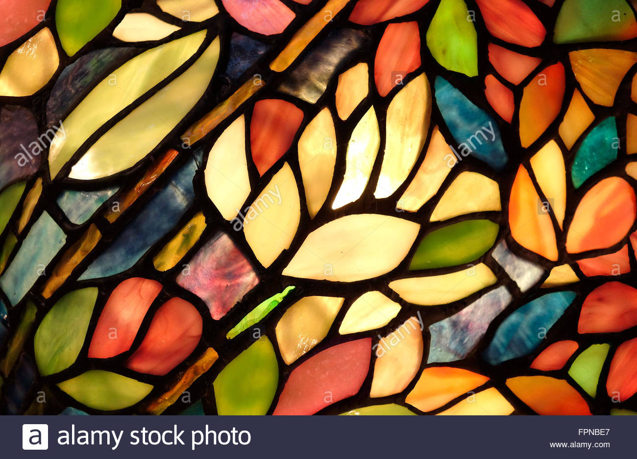 Hand crafted stained glass in a small church window. Very colorful and vibrant art. - Stock Image