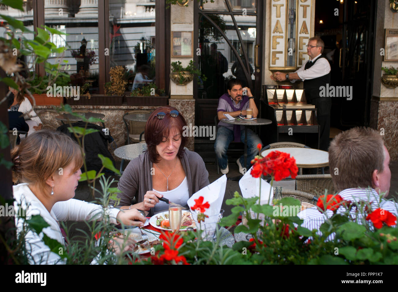 People eating in the terrace of Le Falstaff, Brussels, Belgium. One of the terraces of the many restaurants in Brussels. - Stock Image