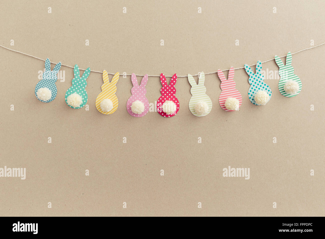 Easter Bunny Banner. Cute bunny shapes with yarn pom pom tails. - Stock Image