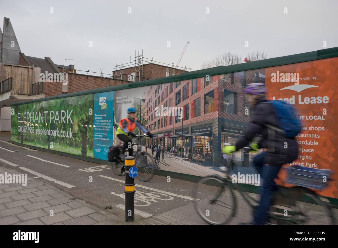 Cyclists go past a new building development at the Elephant and Castle area in south London - Stock Image