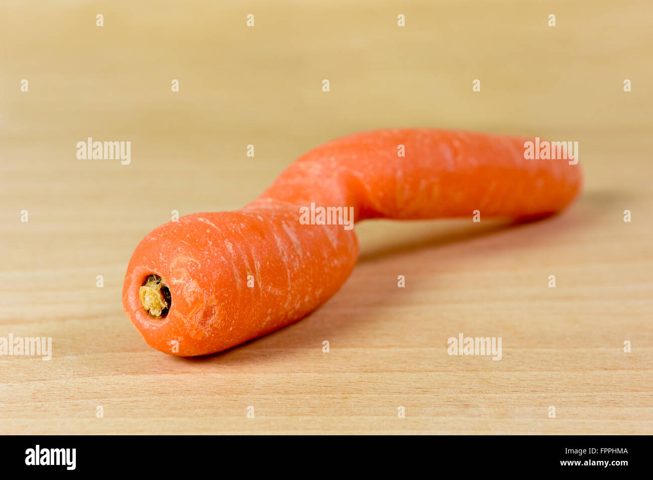 Deformed and misshapen carrot on on chopping board - Stock Image