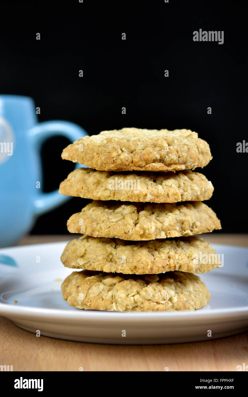 Pile of home made oat cookies on plate with edge of blue mug against a black background - Stock Image