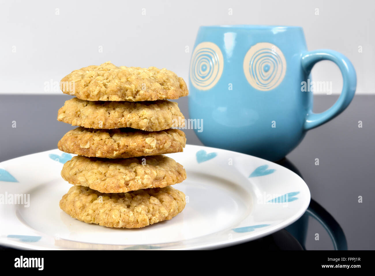 Pile of home made oat cookies on plate on black work top with blue mug - Stock Image
