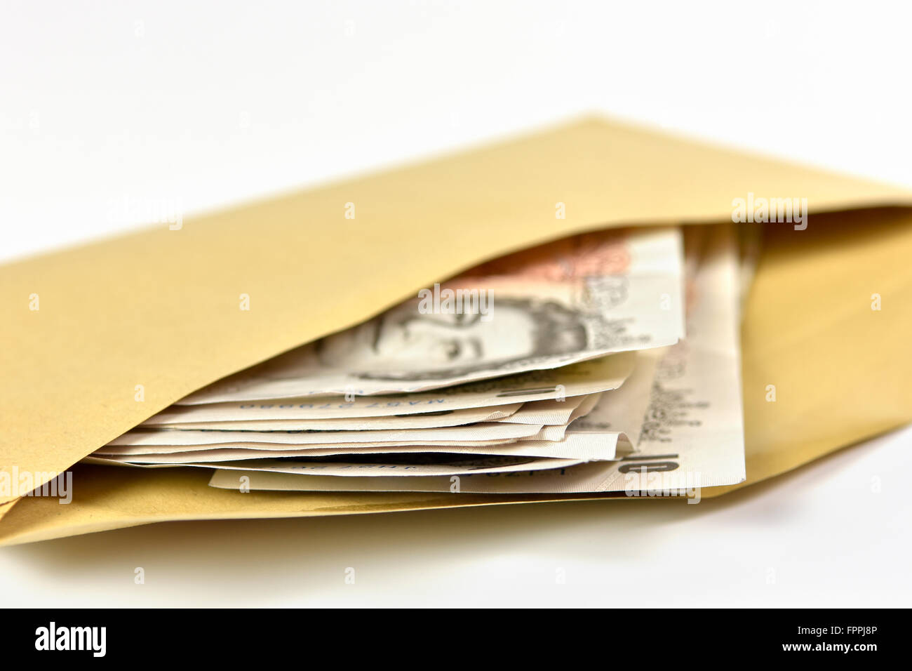 Wad of bank notes in British Sterling currency in brown envelope, mainly £10 notes - Stock Image