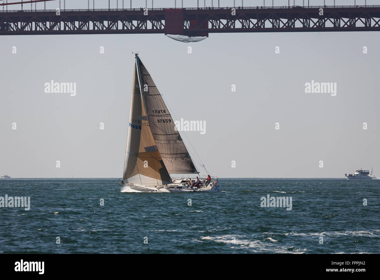 sailboat sails swiftly by the San Francisco Golden Gate Bridge - Stock Image