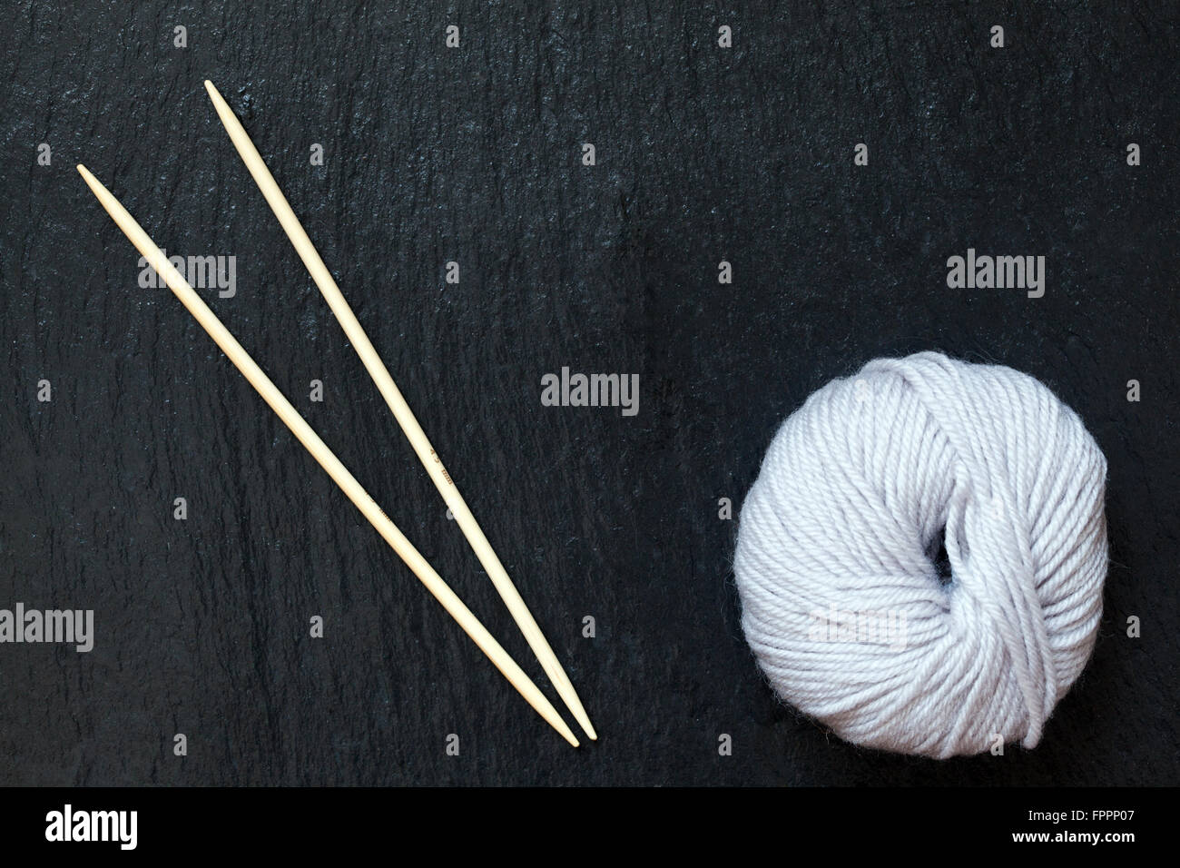 skein of white yarn with bamboo knitting needles with black slate background - Stock Image