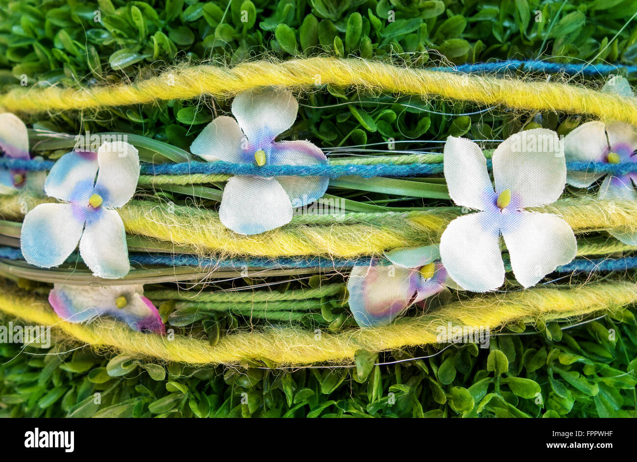 Decoration of fabric flowers and wool threads on an artificial green bush in close-up - Stock Image
