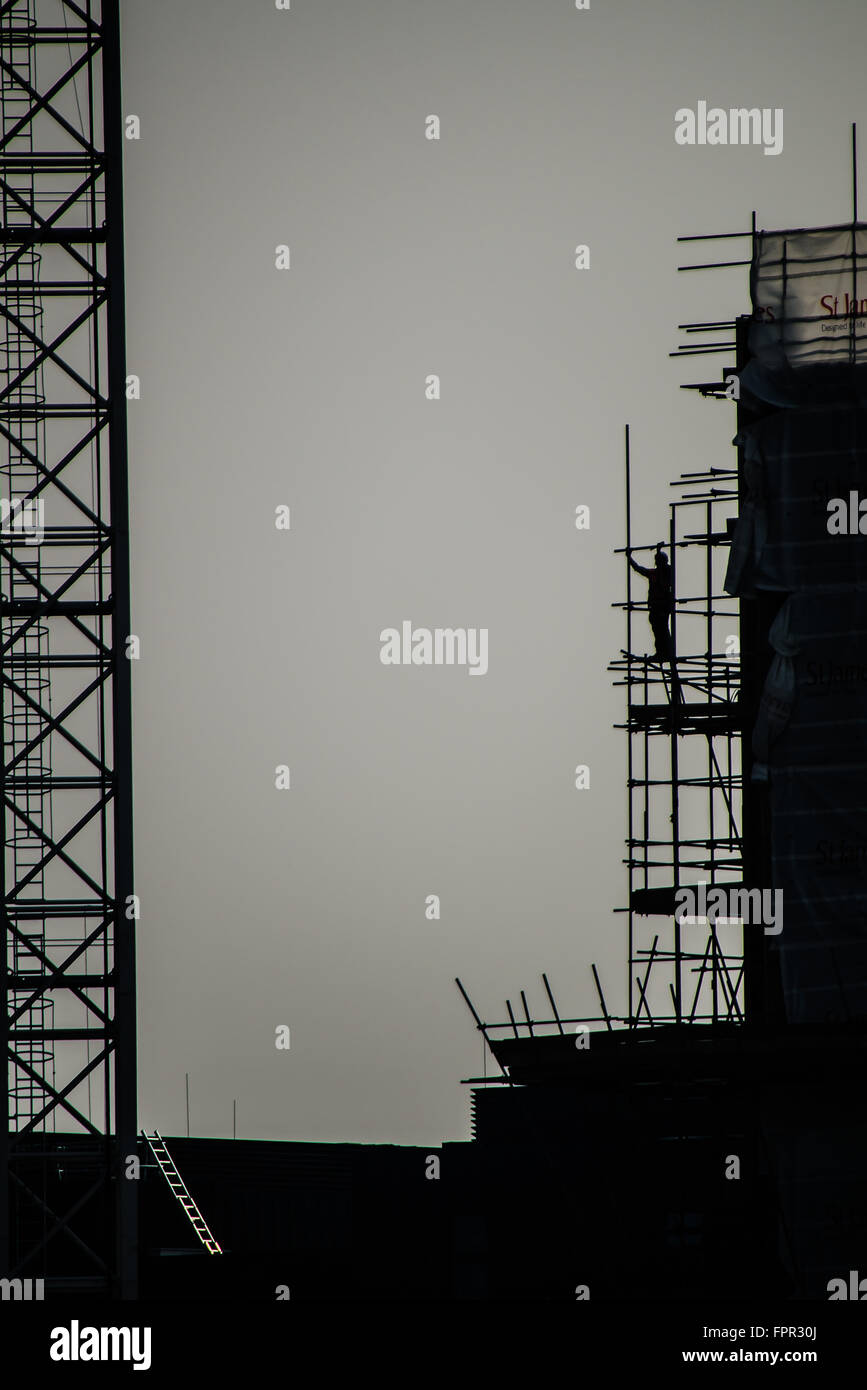 A scaffolder works at height erecting scaffolding on the south bank of the Thames near Battersea. Scaffold. Silhouette. - Stock Image