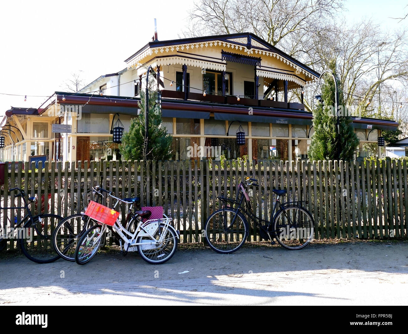Cafe Groot Melkhuis in Vondelpark on a sunny cold day. Typical Dutch bikes are parked at fence - Stock Image
