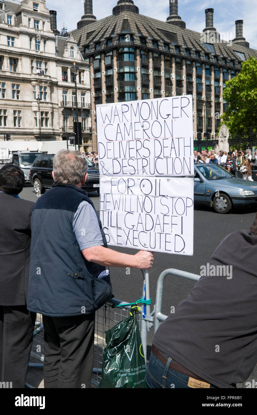 A demonstrator in Parliament Square, London holding a placard bearing a prediction about the fate of Colonel Gadaffi - Stock Image