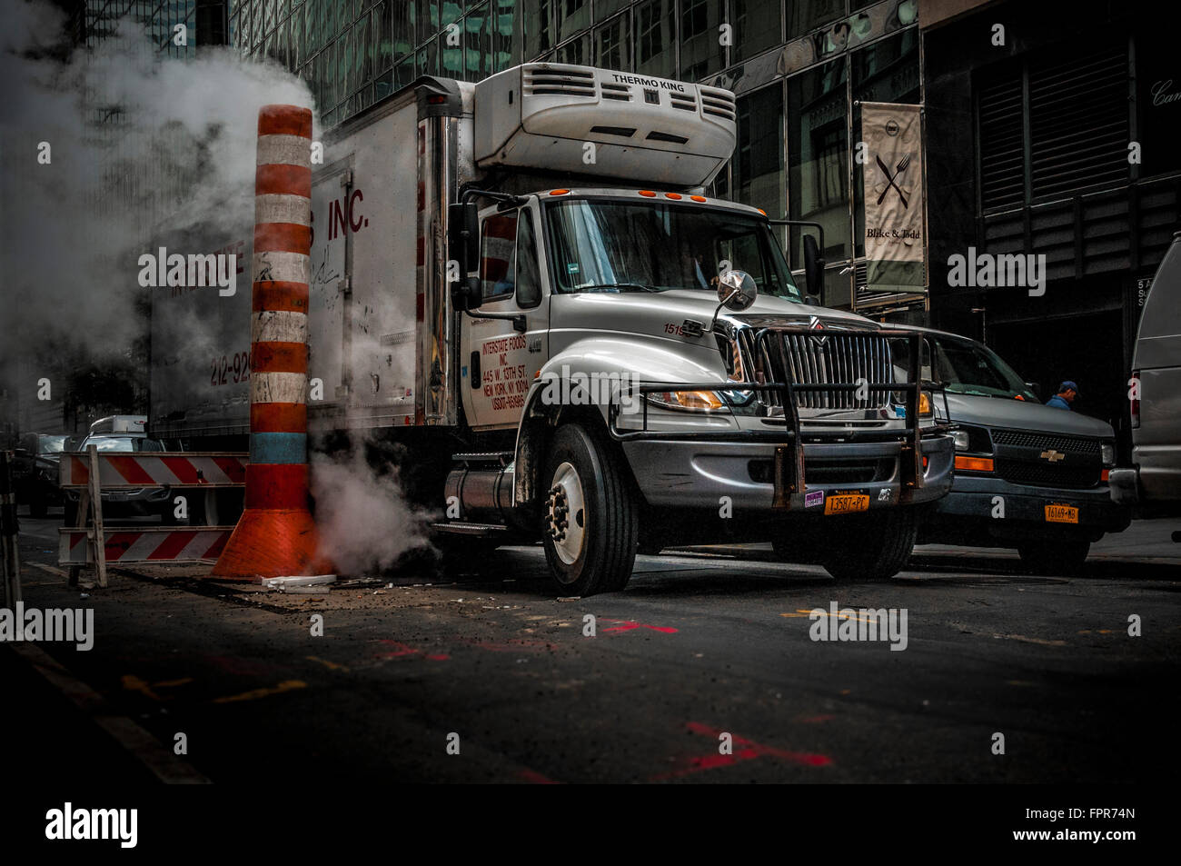 Truck and Steam vapor being vented through a typical Con Edison orange and white stack, New York City, USA. - Stock Image