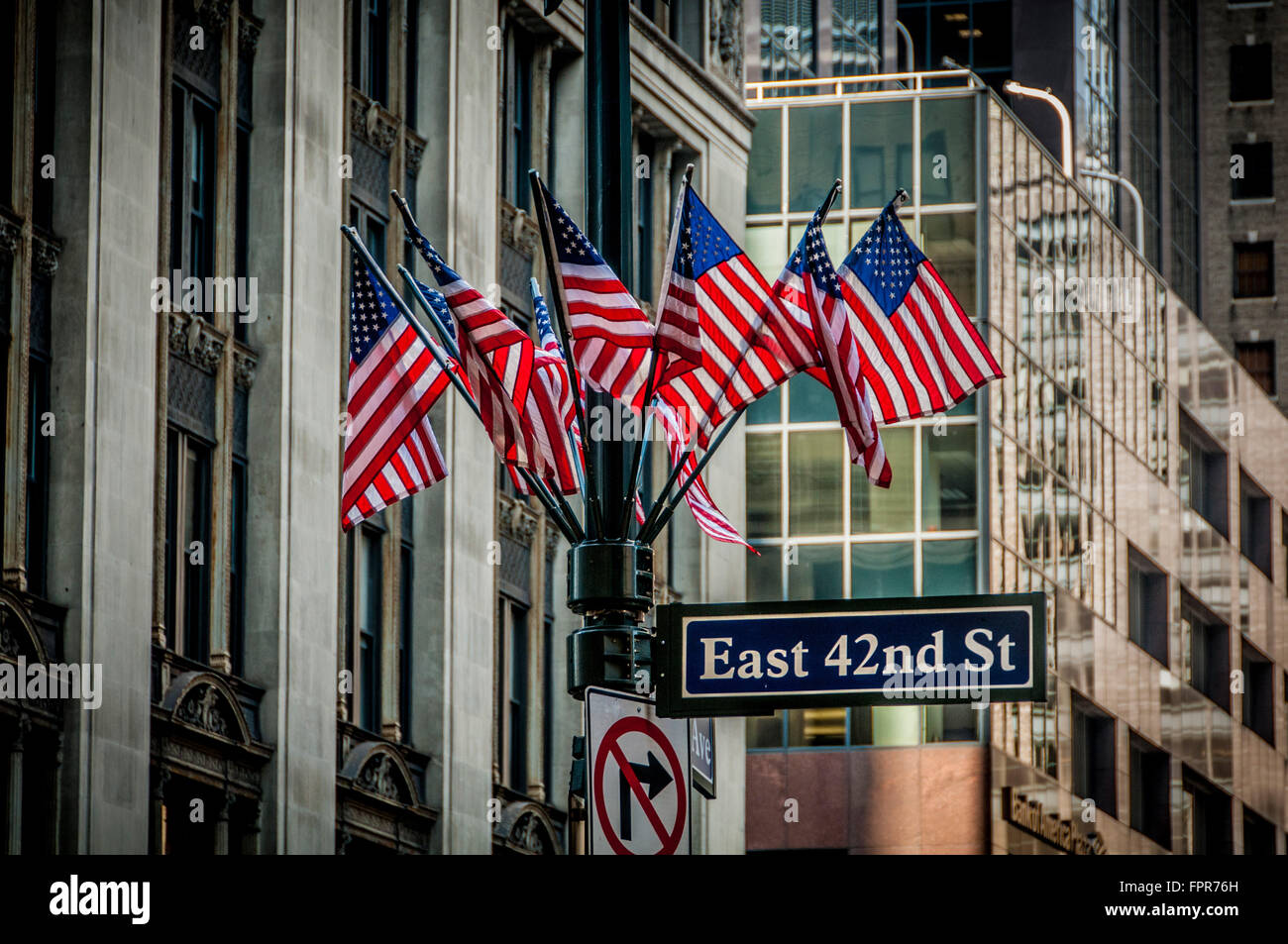 East 42nd St sign and group of American flags on lampost, New York City, USA. - Stock Image