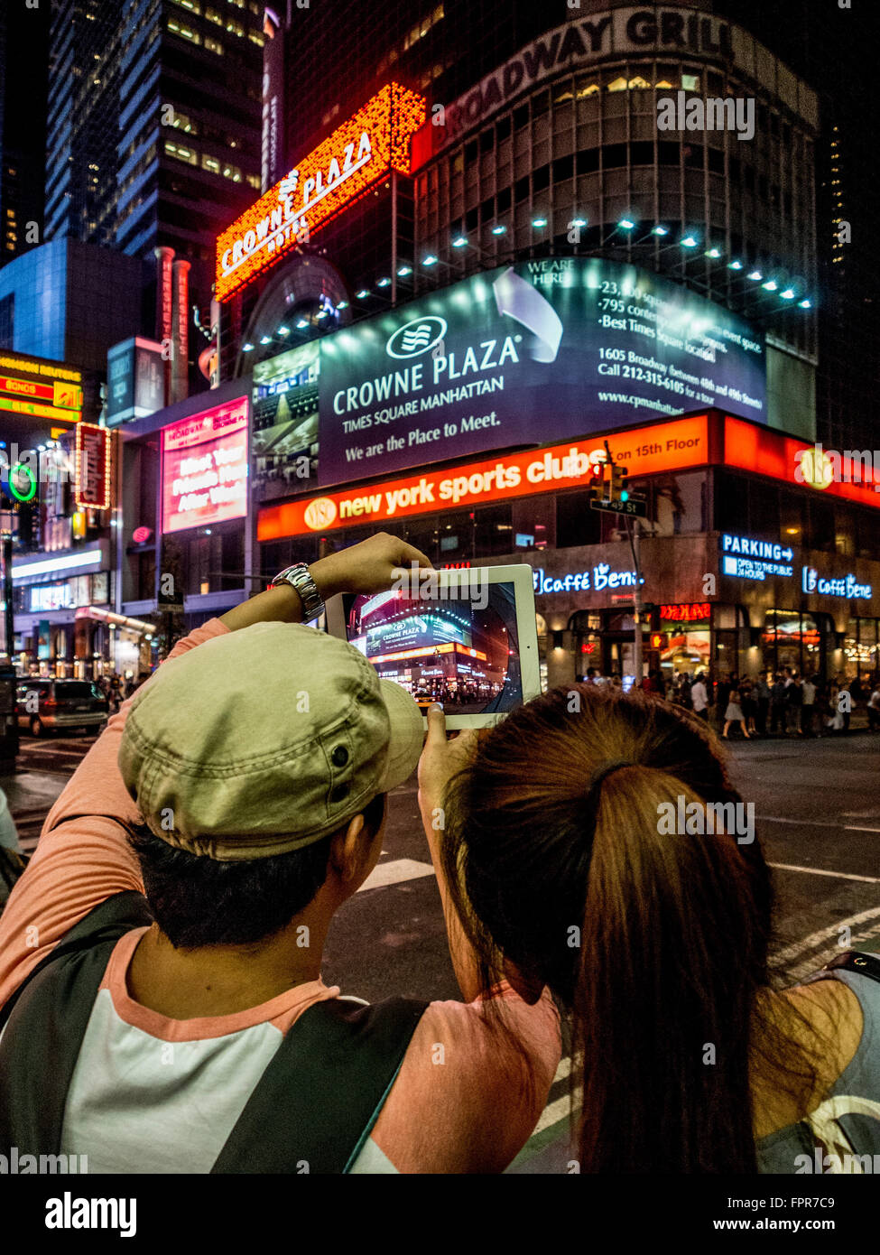 Couple taking photo on ipad of Times Square at night, New York City, USA. - Stock Image
