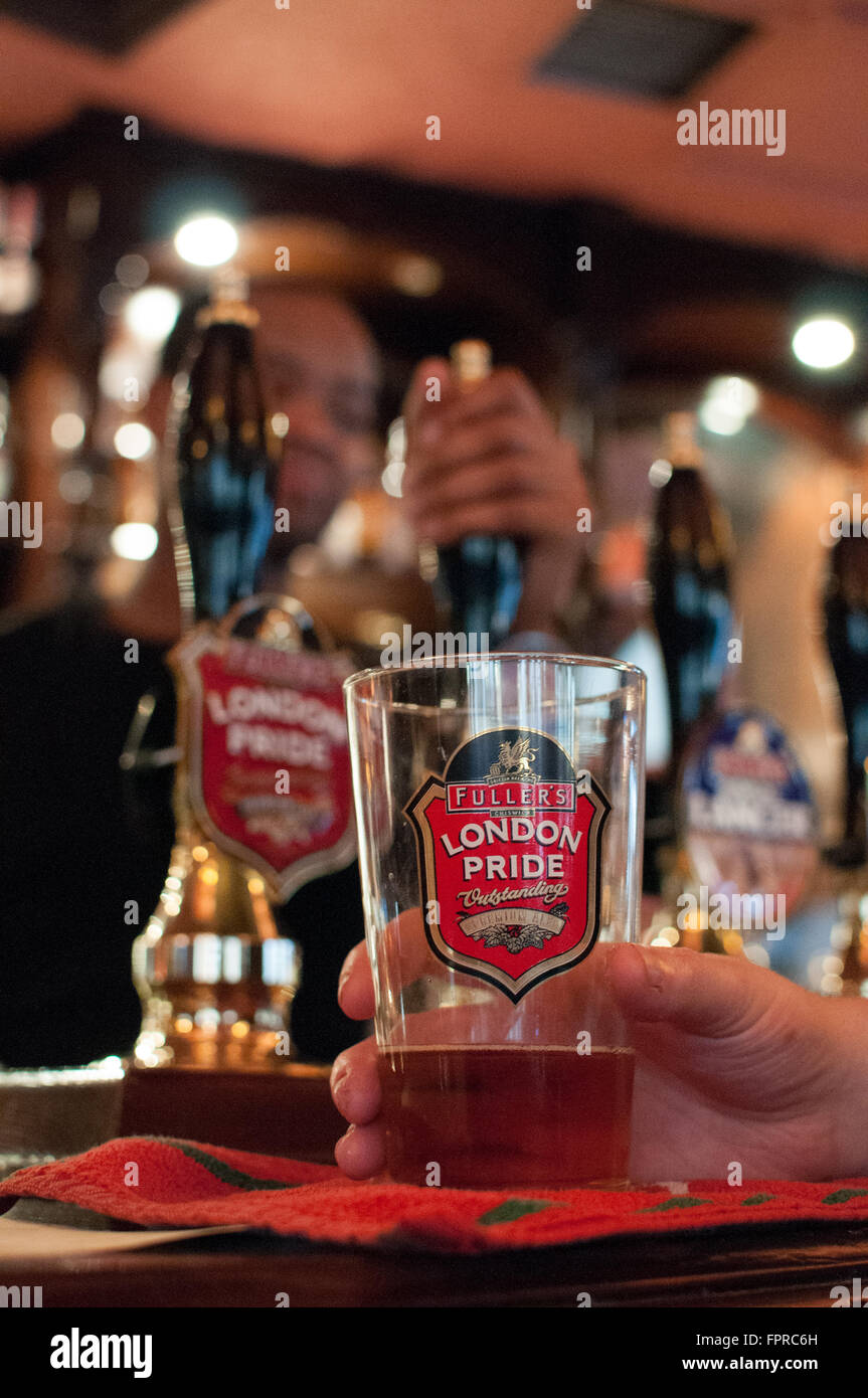 Fuller's Brewery London Pride Pint on Bar Counter by held by customer. - Stock Image