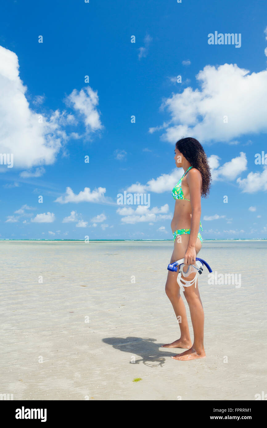 Solo mixed race traveler with a snorkel and mask on a beautiful, empty tropical beach - Stock Image
