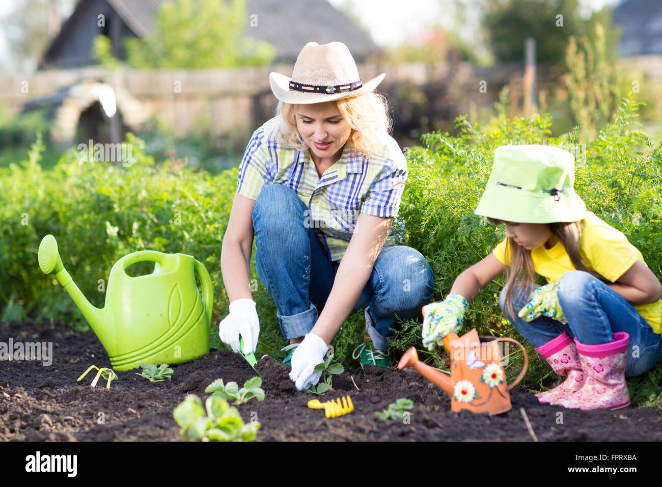 Kid with mother planting seedlings in garden Stock Photo