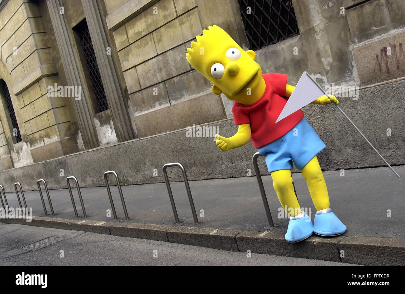 Life size Bart Simpson cartoon character leaning on bike rack with blank triangular flag in hand - Stock Image