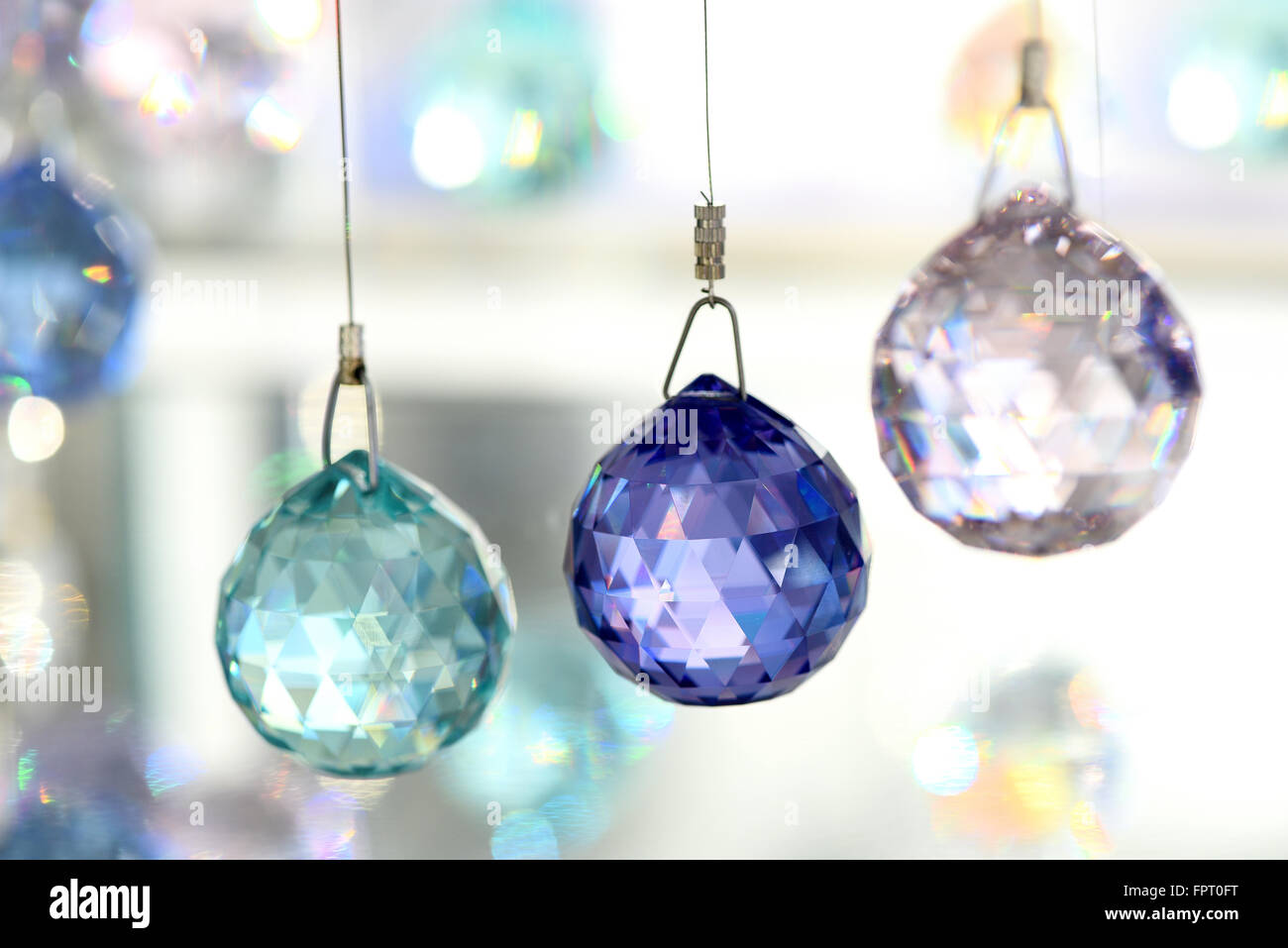 Selective focus close up of green, blue and clear crystal ornaments hung on string in store display - Stock Image