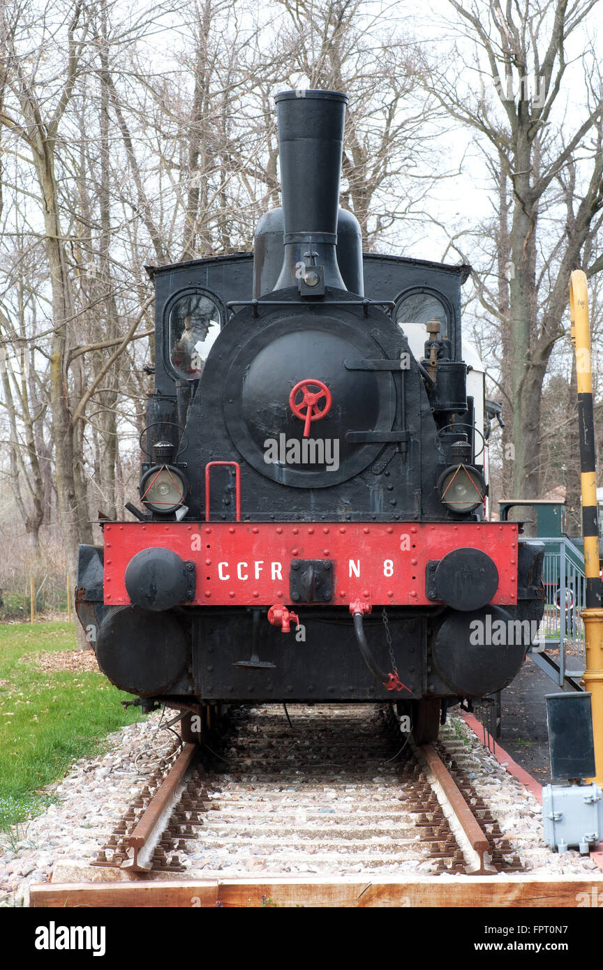 Front view on single old fashioned steam powered locomotive in outdoor museum display during winter - Stock Image