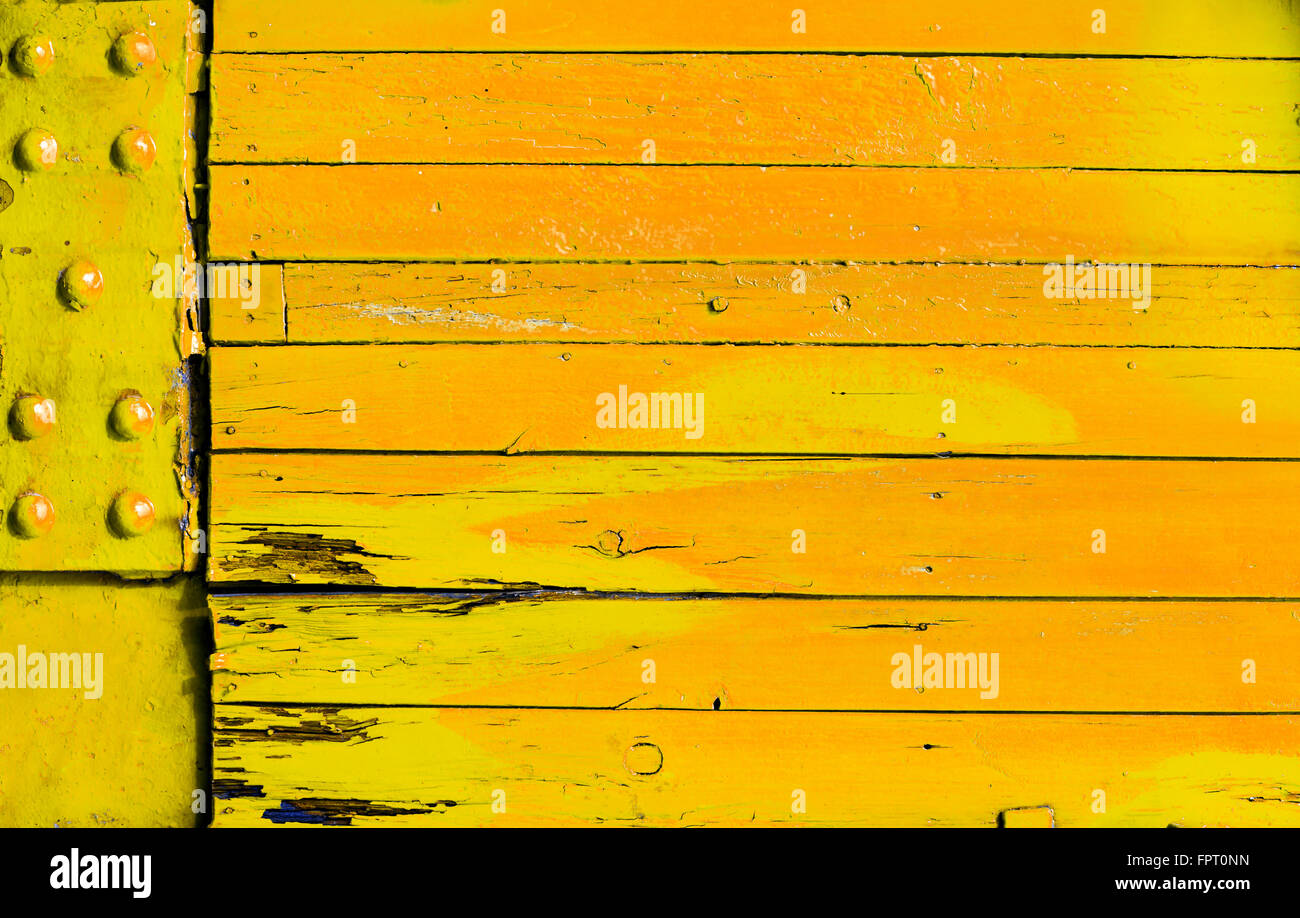 Brightly colored yellow orange wood background with grunge cracked boards and a metal plate with rivets in a full - Stock Image