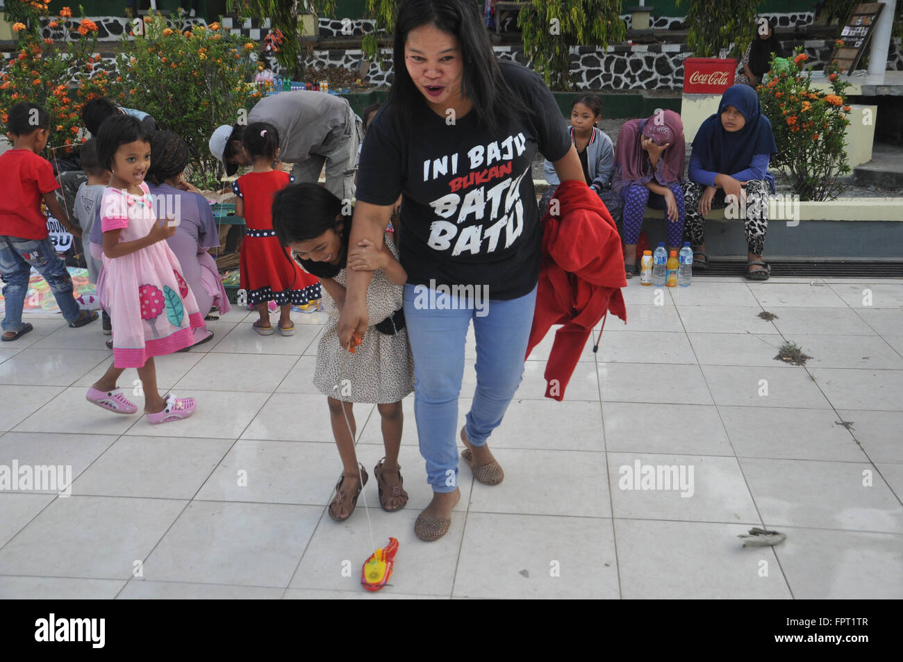 Makassar, Indonesa. Mother and son play at a public space. - Stock Image