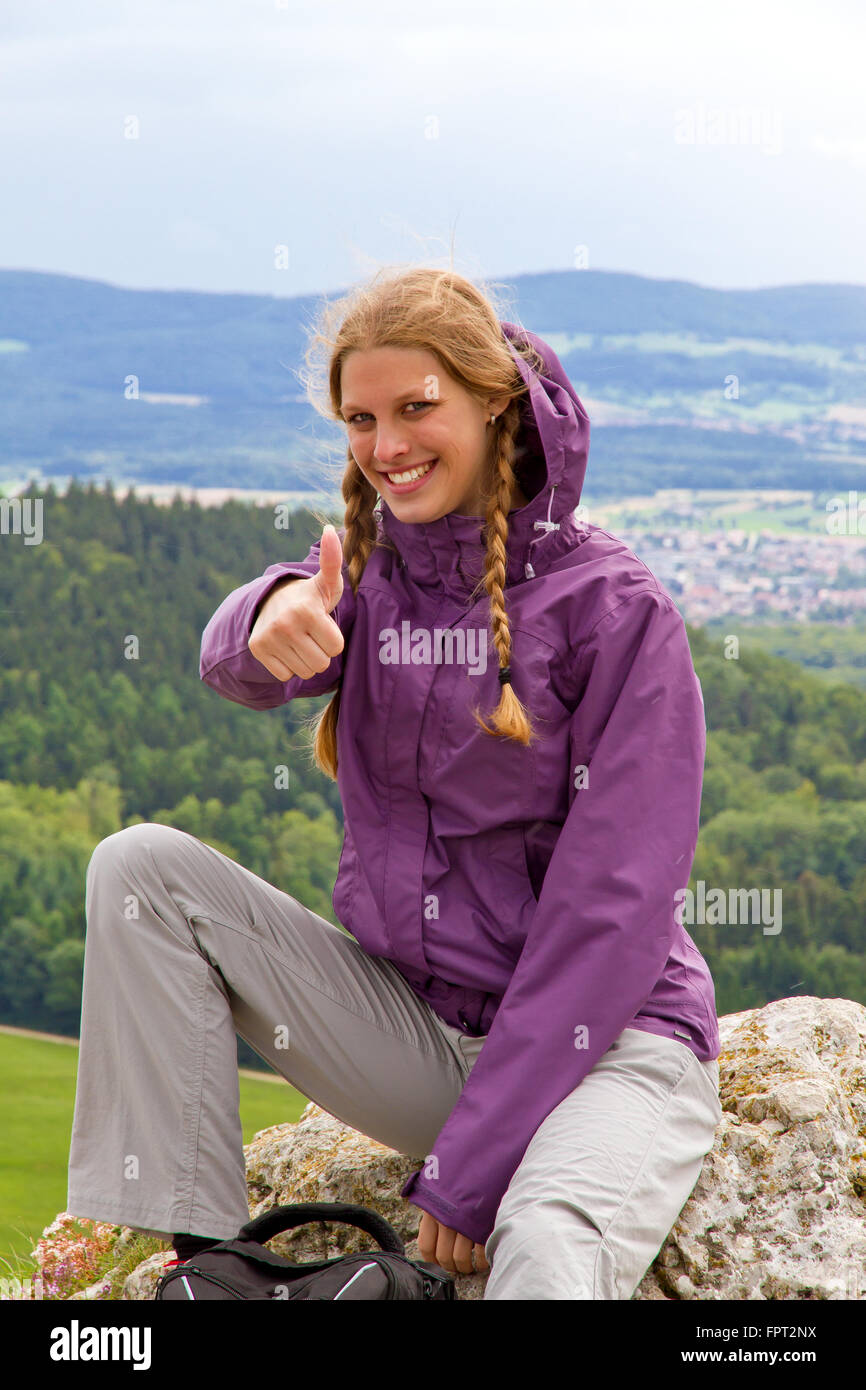 Young, happy woman with thumb up sitting on top of the mountain - Stock Image