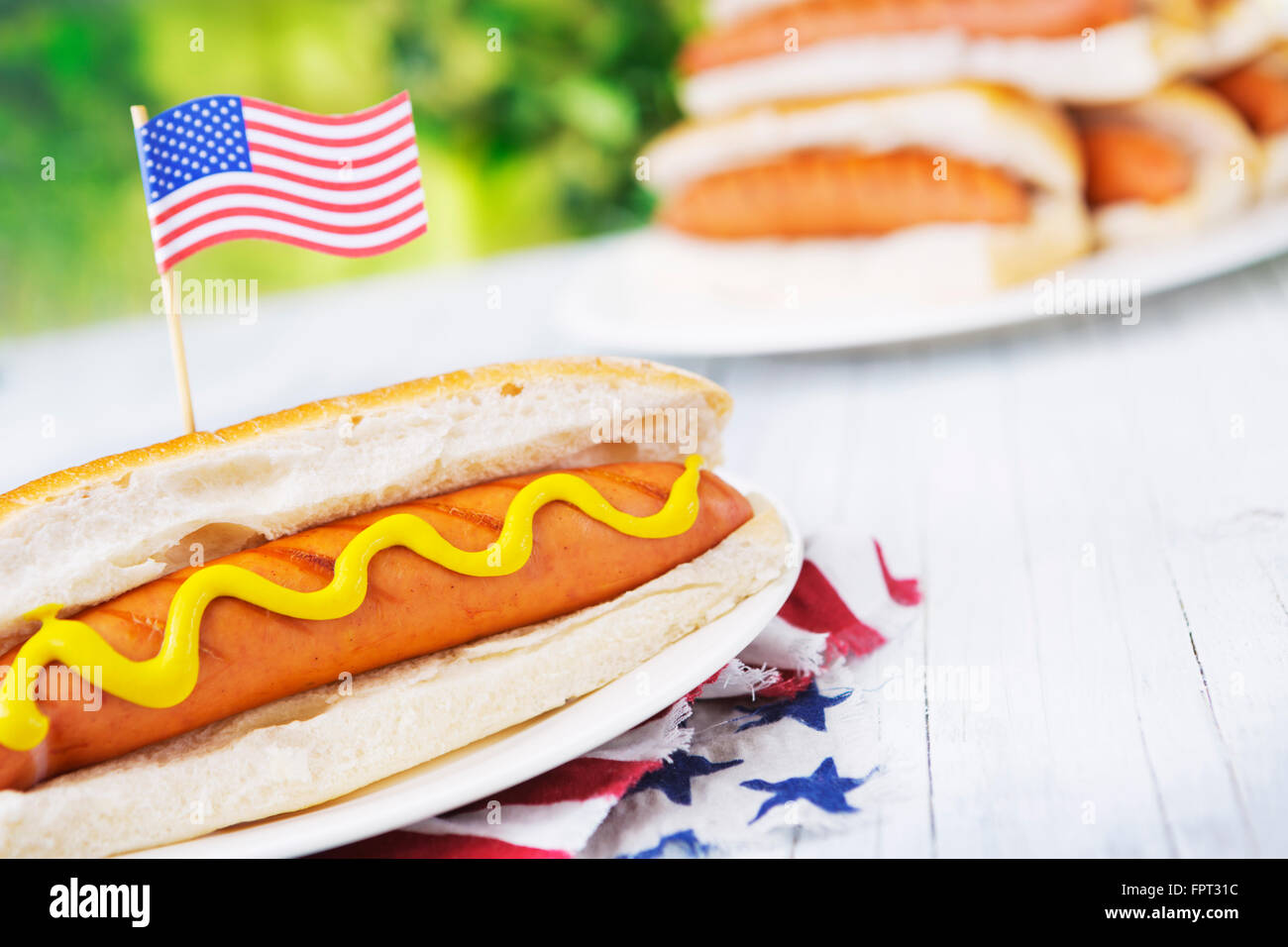 A tasty hot dog with mustard on an outdoor table. - Stock Image
