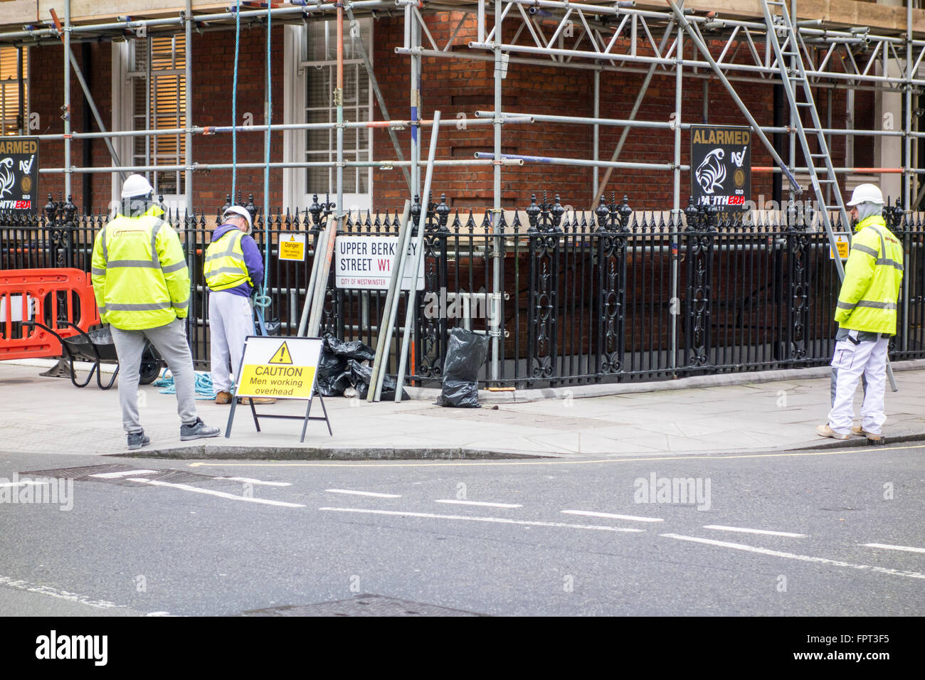 Scaffolders working outside a building in London wearing PPE personal protective equipment, UK Stock Photo