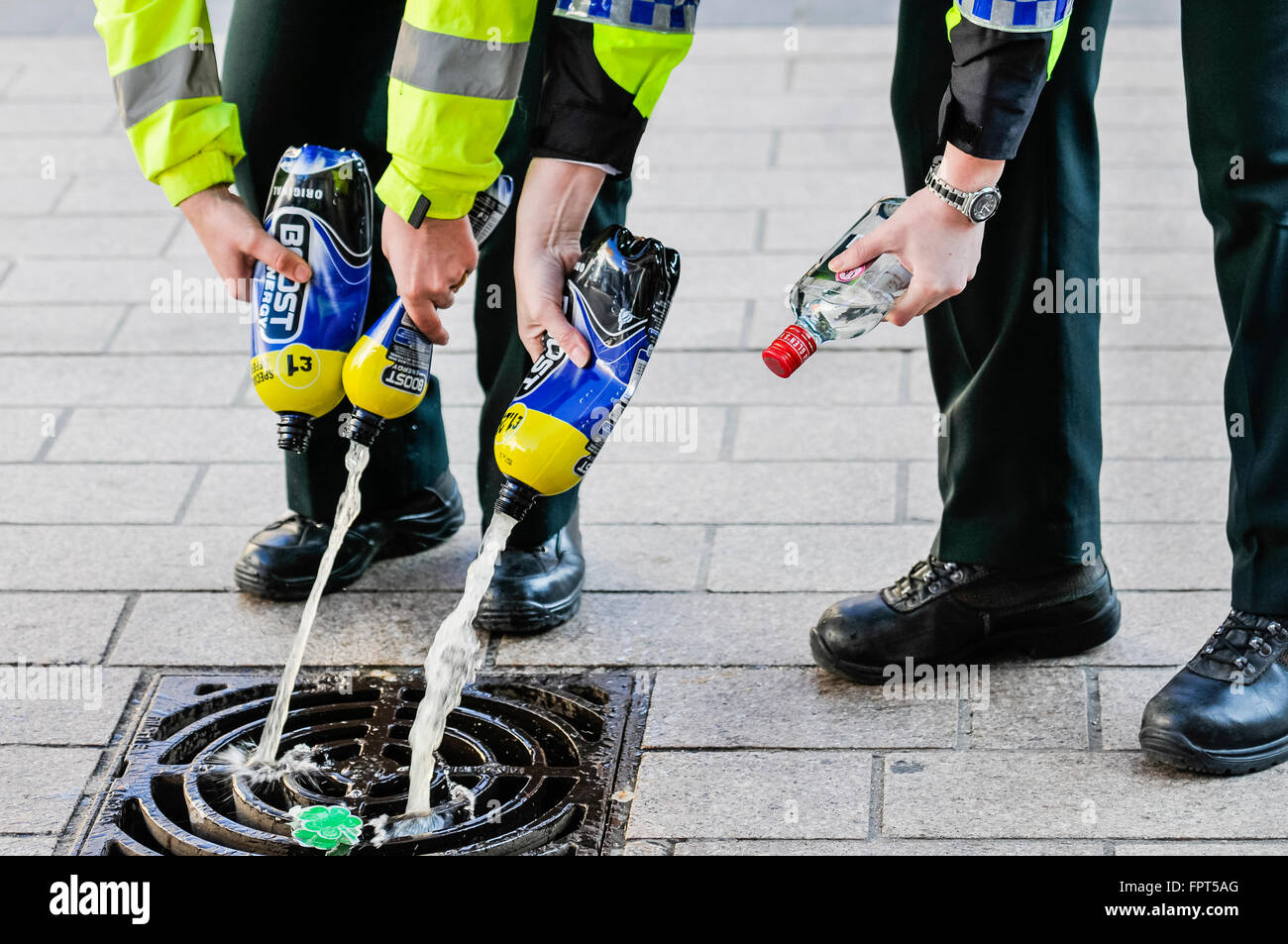 Belfast, Northern Ireland. 17 Mar 2016 - PSNI police officers dispose of alcohol confiscated from youths. Stock Photo