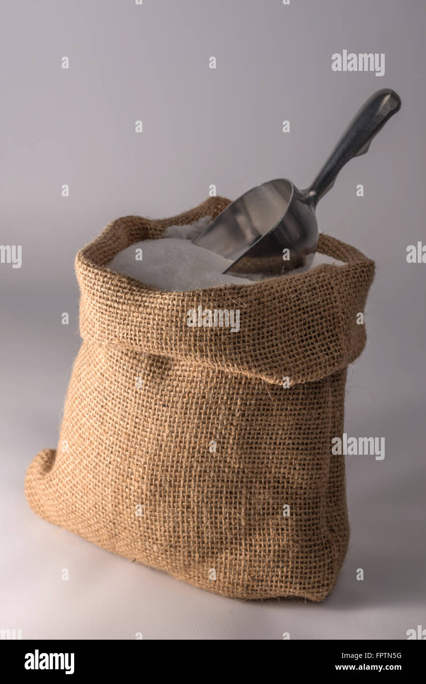 Small open sack of sugar with a metal scoop - Stock Image