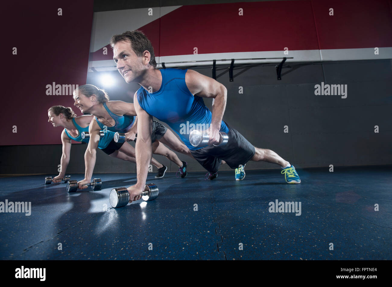 Athletes doing push ups in the gym by holding dumbbell, Bavaria, Germany - Stock Image
