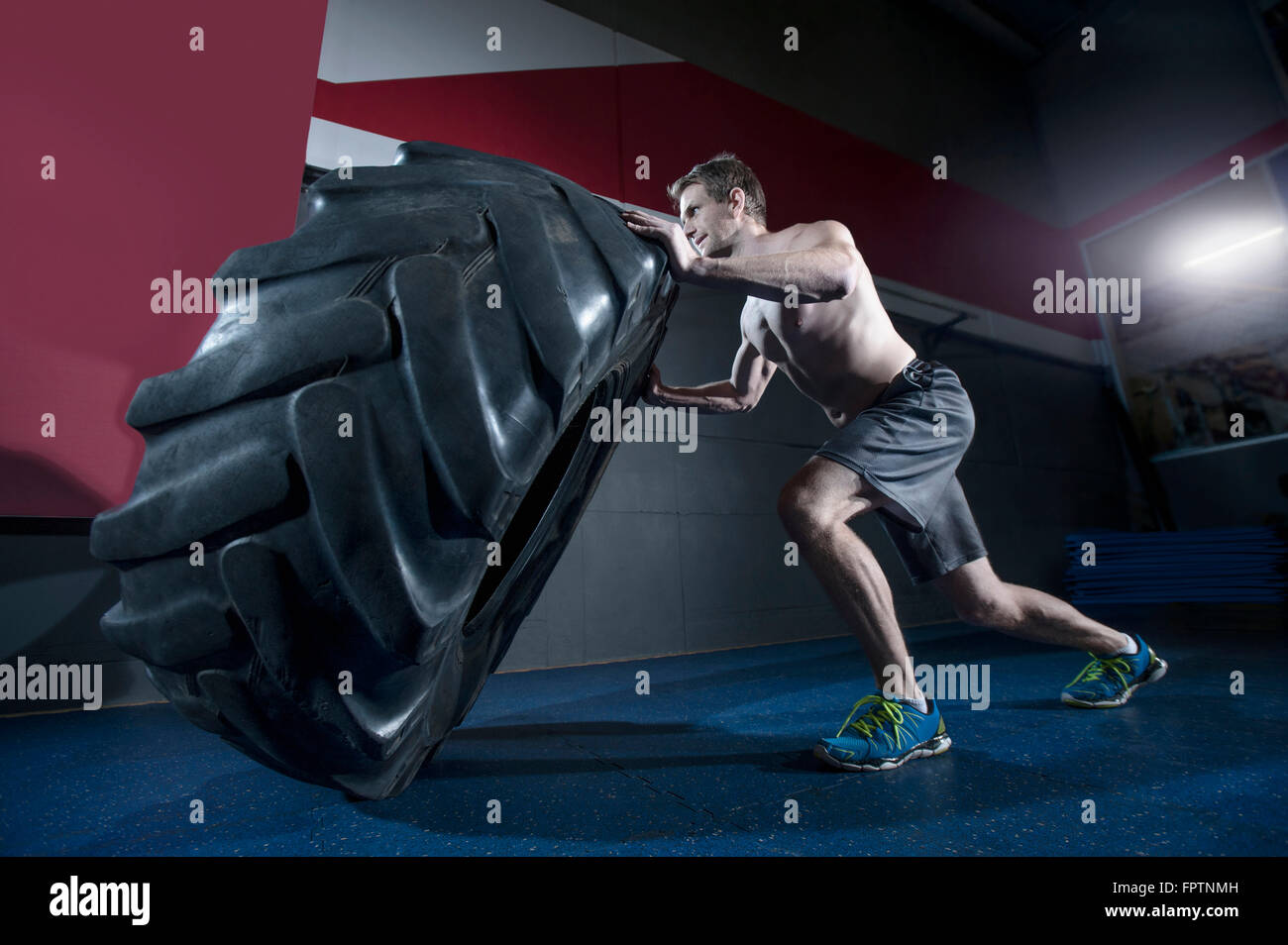 Man training with the tractor wheel in the gym, Bavaria, Germany - Stock Image
