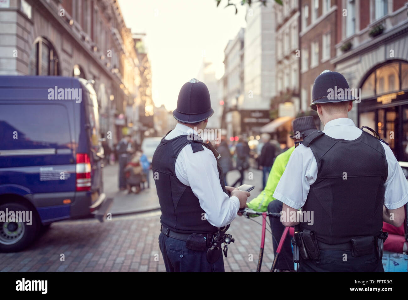 British police officers in helmets policing London streets - Stock Image