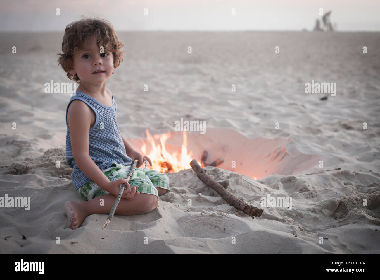 Boy sitting next to camp fire on beach and family in the background, Lit-et-Mixe, Aquitaine, France - Stock Image
