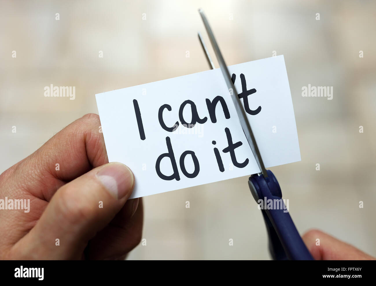 Man using scissors to remove the word can't to read I can do it concept for self belief, positive attitude and - Stock Image
