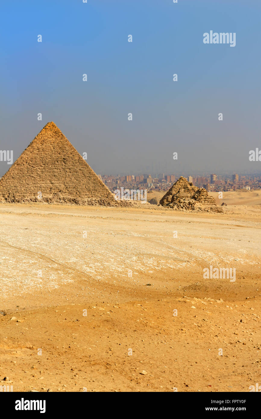 The Pyramids of Giza, man-made structure from Ancient Egypt in the golden sands of the desert with polluted Cairo - Stock Image