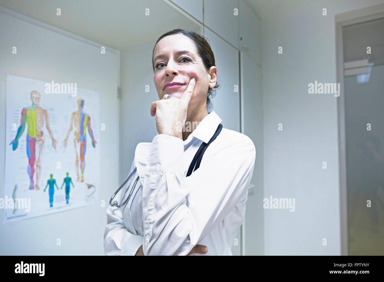 Female doctor thinking with hand on chin, Freiburg Im Breisgau, Baden-Württemberg, Germany - Stock Image