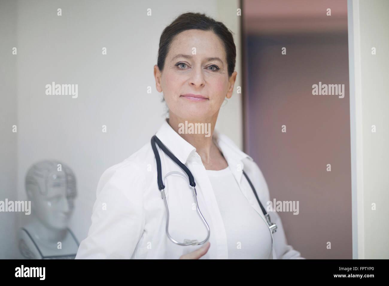 Portrait of a confident female doctor with stethoscope, Freiburg Im Breisgau, Baden-Württemberg, Germany - Stock Image