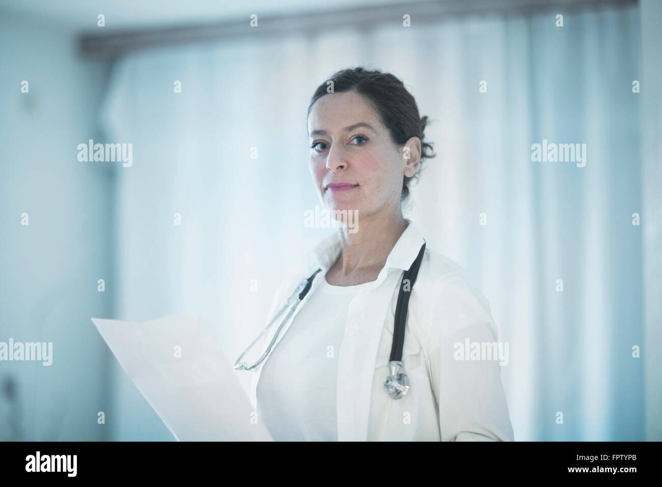 Portrait of a confident female doctor holding a medical report, Freiburg Im Breisgau, Baden-Württemberg, Germany - Stock Image