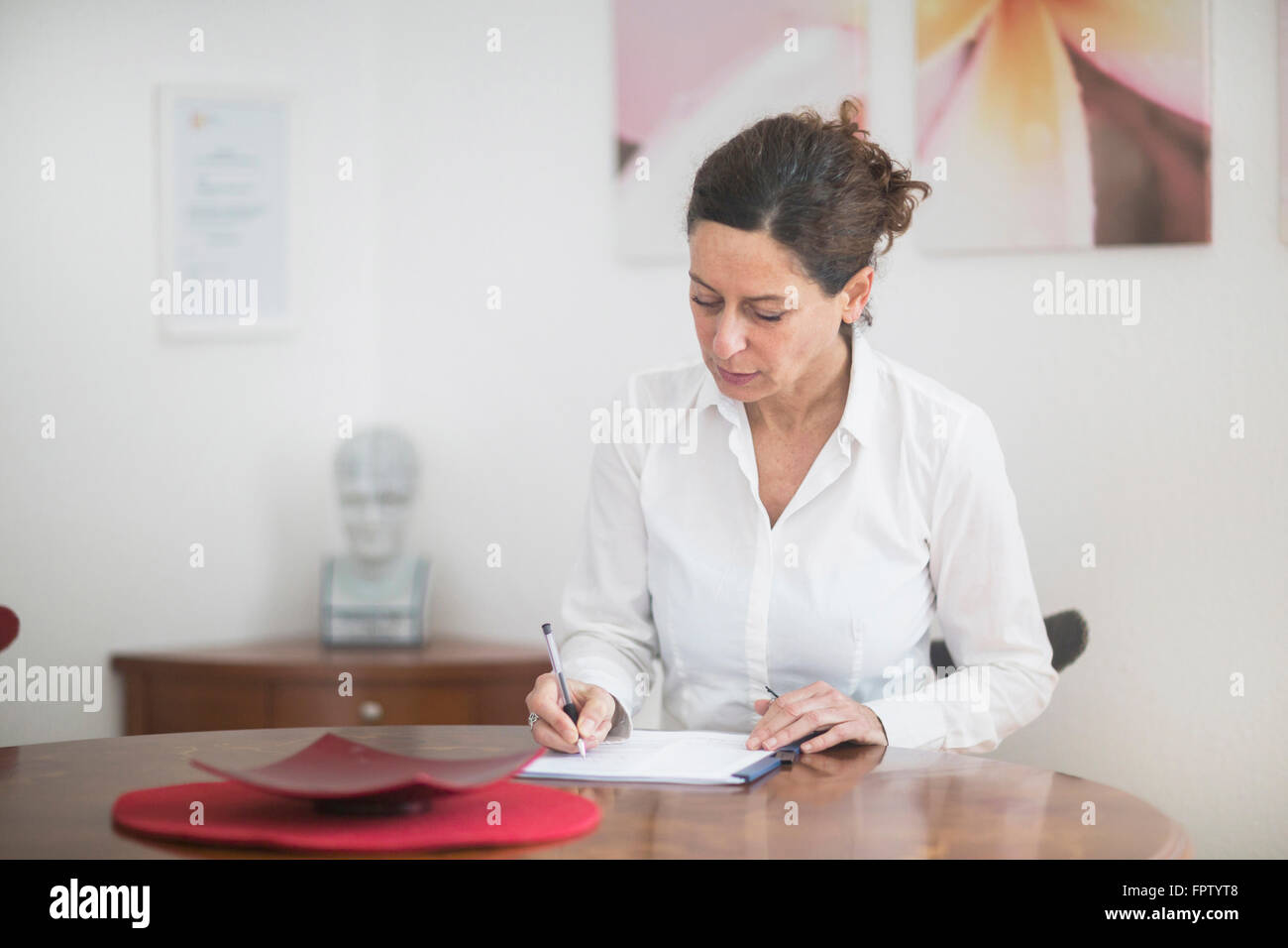 Female doctor writing prescription in hospital, Freiburg Im Breisgau, Baden-Württemberg, Germany - Stock Image