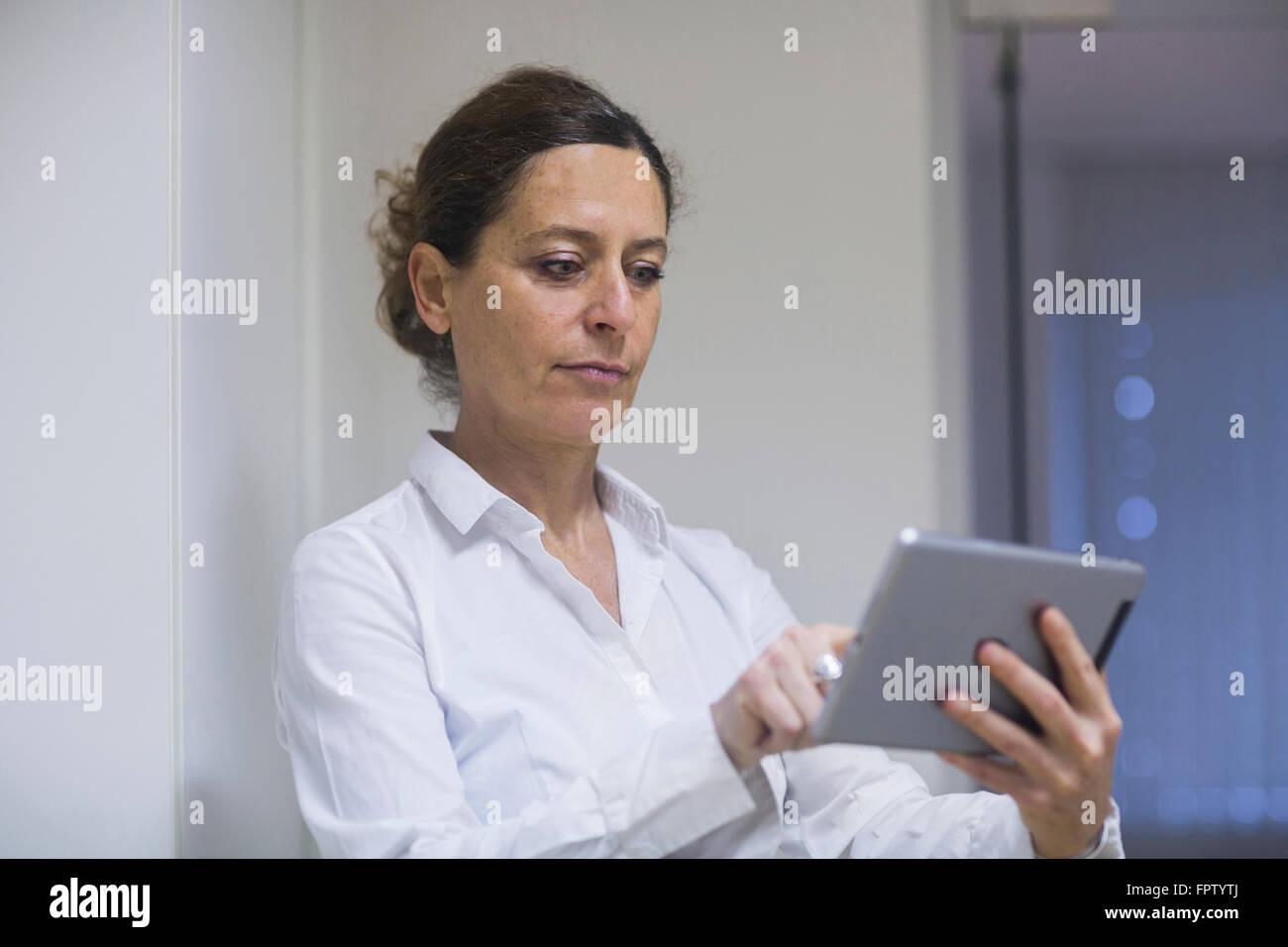 Female physiotherapist using a digital tablet, Freiburg Im Breisgau, Baden-Württemberg, Germany - Stock Image
