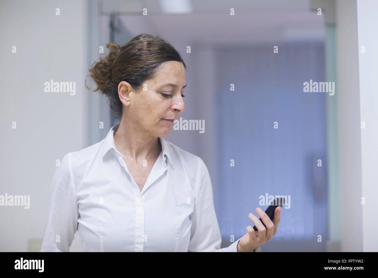Female physiotherapist reading message on a mobile phone, Freiburg Im Breisgau, Baden-Württemberg, Germany - Stock Image