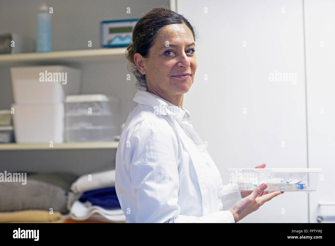 Portrait of a female doctor holding a medicine box, Freiburg Im Breisgau, Baden-Württemberg, Germany - Stock Image