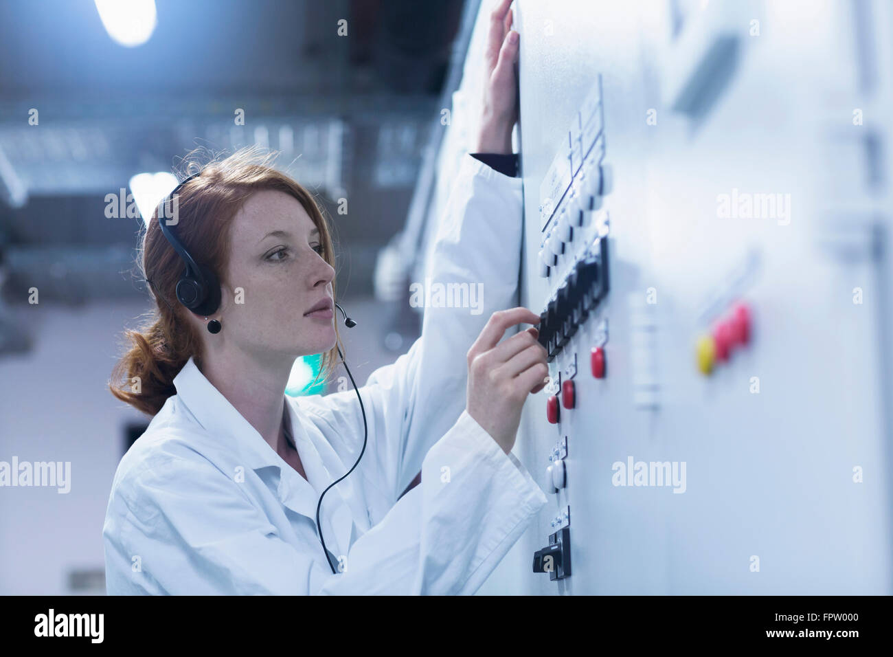 Young female engineer wearing headset and controlling a switch gear in control room, Baden-Württemberg, Germany Stock Photo