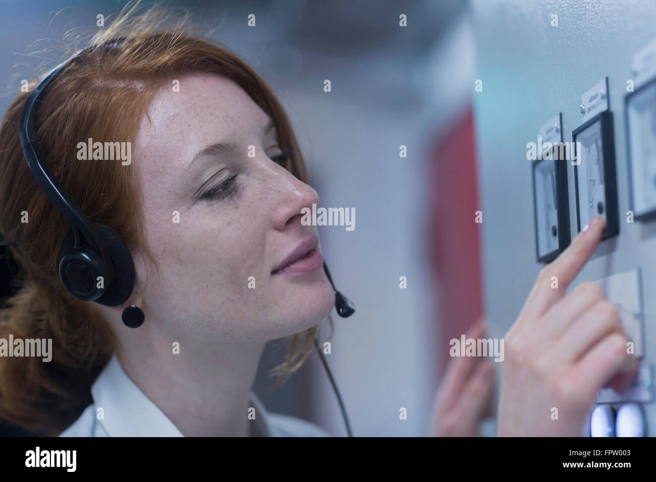 Young female engineer wearing headset and examining in control room, Freiburg Im Breisgau, Baden-Württemberg, - Stock Image
