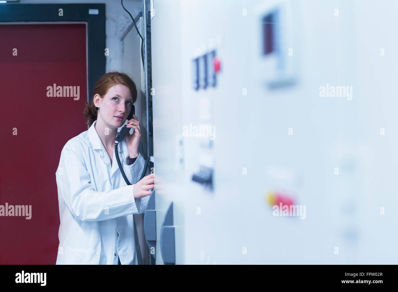 Young female engineer talking on landline phone in control room, Freiburg Im Breisgau, Baden-Württemberg, Germany - Stock Image