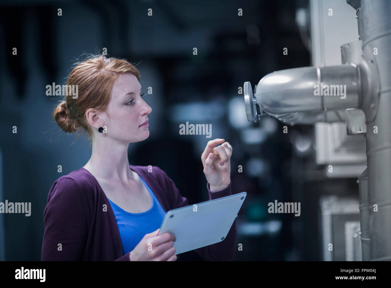 Young female engineer controlling a switchgear in control room, Freiburg Im Breisgau, Baden-Württemberg, Germany - Stock Image