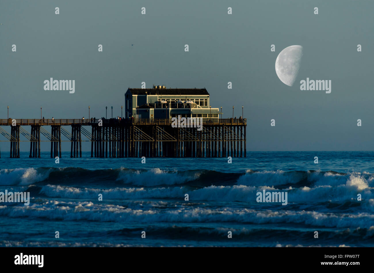 Pier in background with large moon at end of pier, ocean waves crashing into shore. Stock Photo