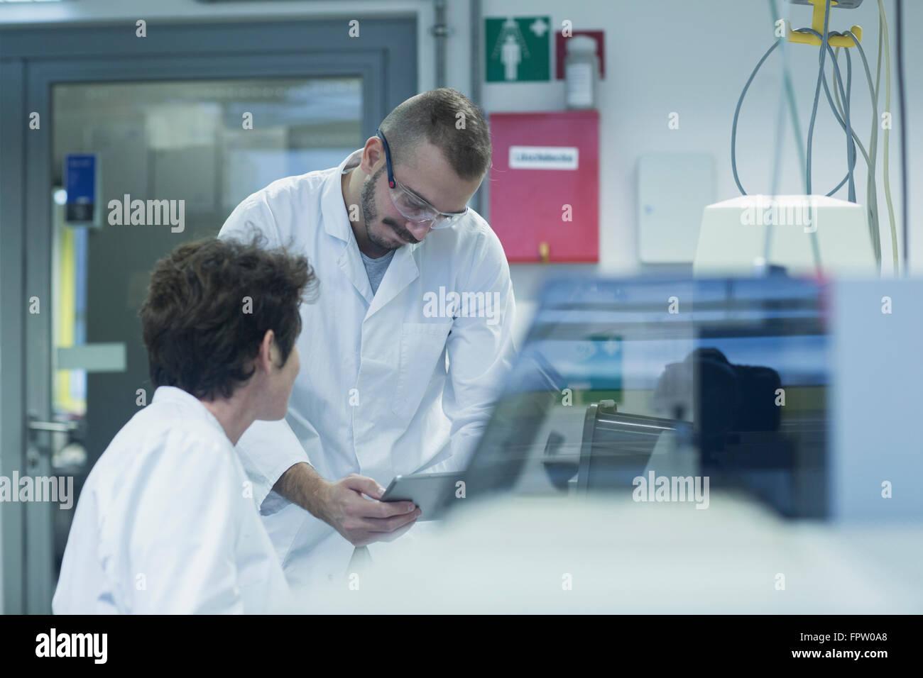 Two scientist working on digital tablet in a pharmacy laboratory, Freiburg Im Breisgau, Baden-Württemberg, - Stock Image