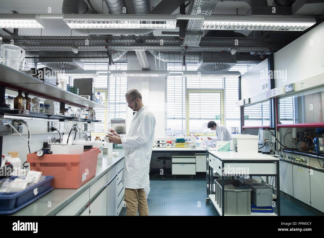 Male scientists working in a pharmacy laboratory, Freiburg Im Breisgau, Baden-Württemberg, Germany - Stock Image